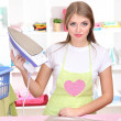 Young girl ironing in room - Stock Photo