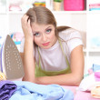 Young girl tired ironing in room - Stock Photo
