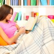 Portrait of female with cup of tea reading book while lying on couch — Foto de Stock
