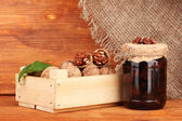 Jam-jar of walnuts and wooden box on wooden background — Stock Photo