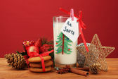 Cookies for Santa: Conceptual image of ginger cookies, milk and christmas decoration on red background — 图库照片