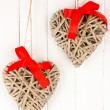 Stock Photo: Wicker hearts with red bow on wooden background