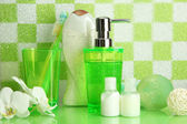 Bath accessories on shelf in bathroom on green tile wall background — Stock Photo