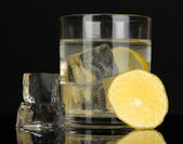 Ice cubes in glass with lemon isolated on black — Foto de Stock