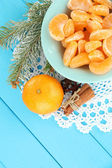 Tasty mandarine's slices on color plate on blue background — 图库照片