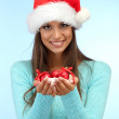 Beautiful young woman holding snow with christmas balls, on blue background — Stockfoto