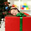 Little girl with large gift box near christmas tree — Stock Photo #17639257