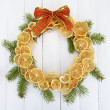 Christmas wreath of dried lemons with fir tree and bow, on white wooden background — Photo