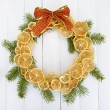 Christmas wreath of dried lemons with fir tree and bow, on white wooden background — Foto Stock
