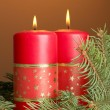 Two candles and christmas tree, on brown background — Stock Photo