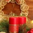 Two candles and christmas decorations, on wooden background - Стоковая фотография
