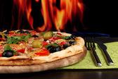 Delicious pizza close-up on wooden table on fire background — Stock Photo
