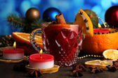 Fragrant mulled wine in glass with spices and oranges around on wooden table on blue background — Stock Photo