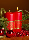 Two candles and christmas decorations, on brown background — Stockfoto