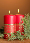 Two candles and christmas tree, on brown background — Stockfoto