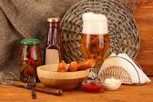 Bier und gegrillten würstchen auf holztisch auf sackleinen-hintergrund — Stockfoto