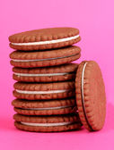 Chocolate cookies with creamy layer on pink background — Stock Photo