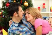 Junge glückliche paar in der nähe von einem weihnachtsbaum zu hause — Stockfoto