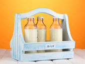 Milk in bottles in wooden box on wooden table on orange background — Stock Photo