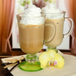 Fragrant coffee latte in glasses cups with vanilla pods, on table in cafe — Stock Photo #17640653