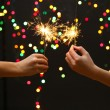 Beautiful sparklers in woman hands on garland background - Stock Photo