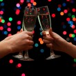 Woman hand with glasses of champagne, on garland background - Stock Photo