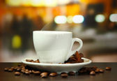 Cup of coffee with beans on table in cafe — Stock Photo