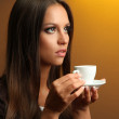 Beautiful young woman with cup of coffee, on yellow background — Stock Photo #17679777