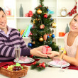 Young happy couple with presents sitting at table near Christmas tree — Stock Photo #17680283