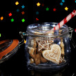 Tasty cookies in glass bottle on blur lights background — Stock Photo #17680979