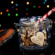 Tasty cookies in glass bottle on blur lights background — Stock Photo