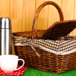 Metal thermos with cup and basket on grass on wooden background — Stock Photo #17682307