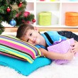 Little boy lying on pillows with gift in his hands under Christmas Tree waiting for Santa Claus to come — Stock Photo #17682819