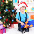 Royalty-Free Stock Photo: Little boy in Santa hat sits near Christmas tree with flippers
