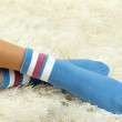 Female legs in colorful socks on  white carpet background - Stock Photo