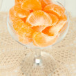 Tasty mandarine's slices in glass bowl on light background - Stock Photo