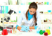 Young scientist looking into microscope in laboratory — Stock Photo