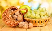 Druva i korg med nötter på träbord — Stockfoto