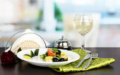 Tasty avocado salad in bowl on wooden table on restaurant background — Stock Photo