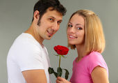 Loving couple with rose on grey background — Stock fotografie