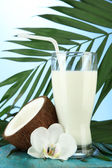 Coconut with glass of milk, on blue background — Stock Photo