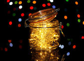Christmas lights in glass bottle on blur lights background — Stock Photo