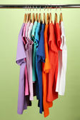 Gran variedad de camisas en perchas de madera, sobre fondo verde — Foto de Stock