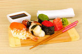 Delicious sushi served on wooden board on bamboo mat — Stock Photo