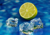 Ice cubes with lime on blue background — Stock Photo