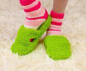 色のスリッパ、カーペットの背景上で女性の足 — ストック写真