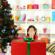 Little girl with large gift box near christmas tree — Stock Photo #17844535