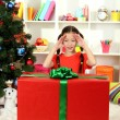 Little girl with large gift box near christmas tree — Lizenzfreies Foto
