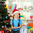 Little girl holding clock near christmas tree - Stock Photo