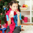 Little girl with pink scarf and glass of milk sitting near christmas tree — Stock Photo #17844553